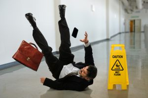 Senior businessman falling near caution sign in hallway
